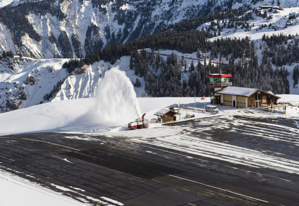 Куршевель Аэропорт. Альтипорт. Small airport altiport runway being cleared of snow by blower on the side of an alpine mountain in winter