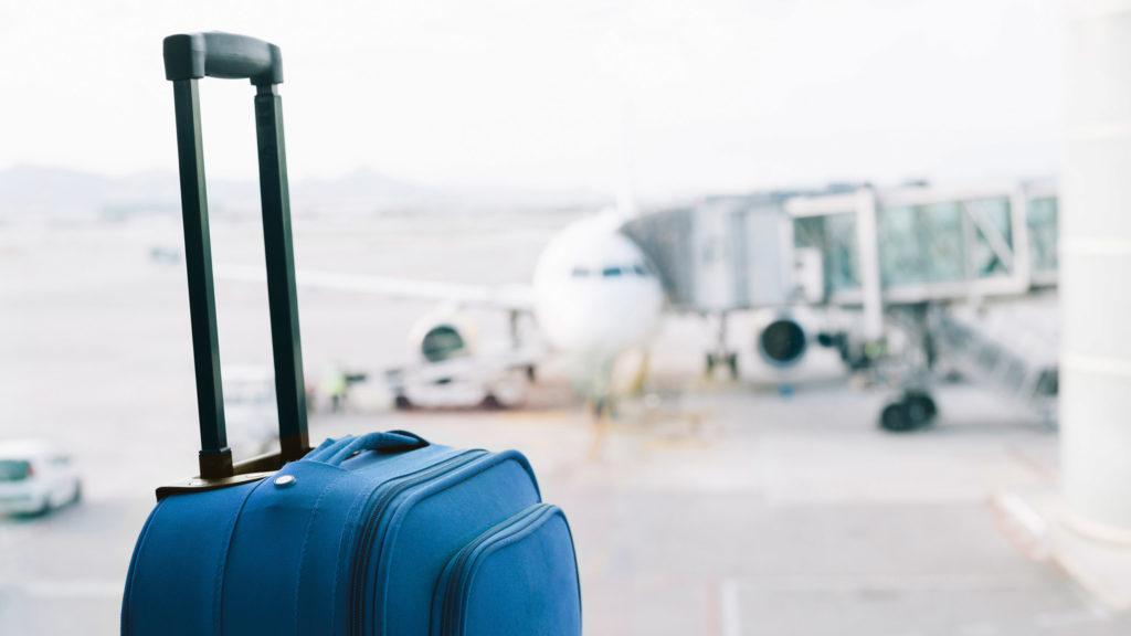 blue suitcase at airport airplane in background 1024x576 - Будущее аэропортов: как прошёл Travel Forum в Гонконге?